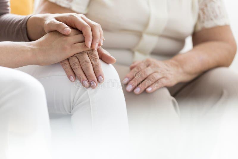 Женщина держа ладонь пенсионера стоковое изображение