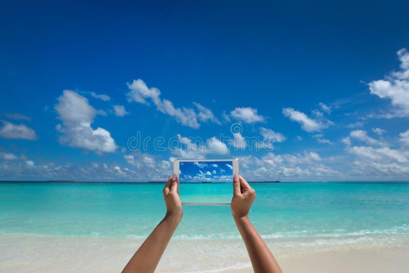 Женщина держа планшет с экраном на тропическом море VT стоковая фотография