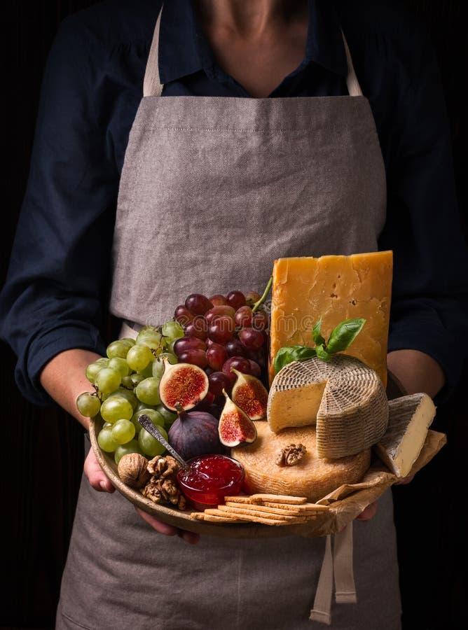 Женщина держа плиту сыра с плодоовощами и вареньем стоковая фотография rf
