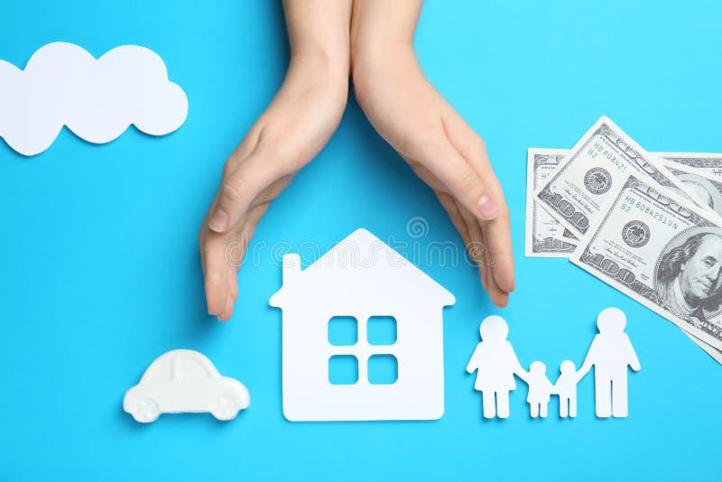 Женщина держа руки над бумажными силуэтами семьи, дома и автомобиля на предпосылке цвета, взгляде сверху стоковая фотография