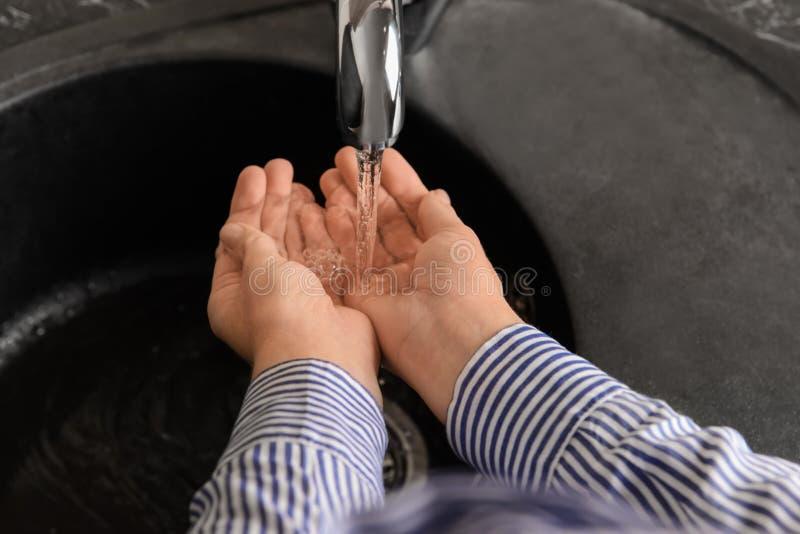 Женщина держа руки под водой бежать от faucet стоковые фото