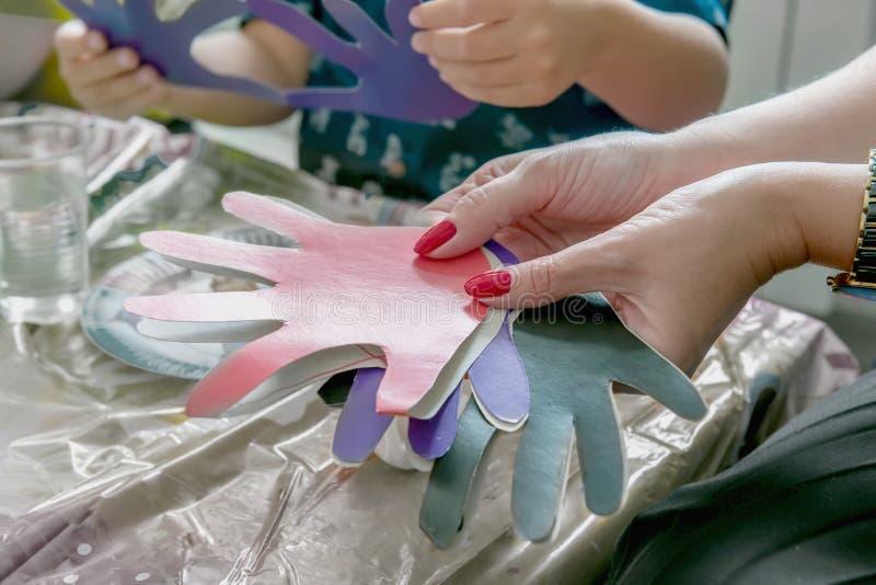 Женщина держа символы ` s детей бумаг-отрезка малые Учитель включен с детьми тренировка стоковое изображение