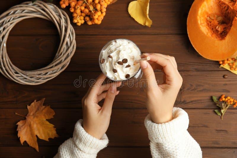 Женщина держа солому и стекло с latte специи тыквы на деревянной предпосылке стоковое изображение rf