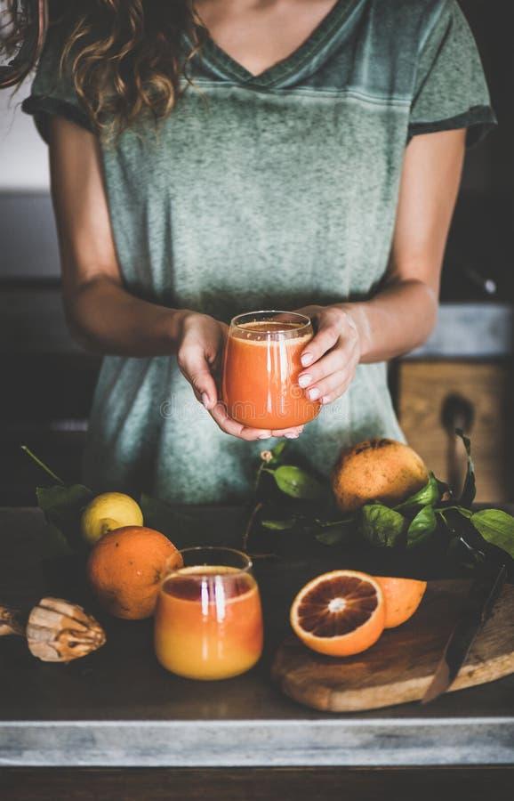 Женщина держа стекло свежих апельсинового сока или smoothie крови стоковые фото