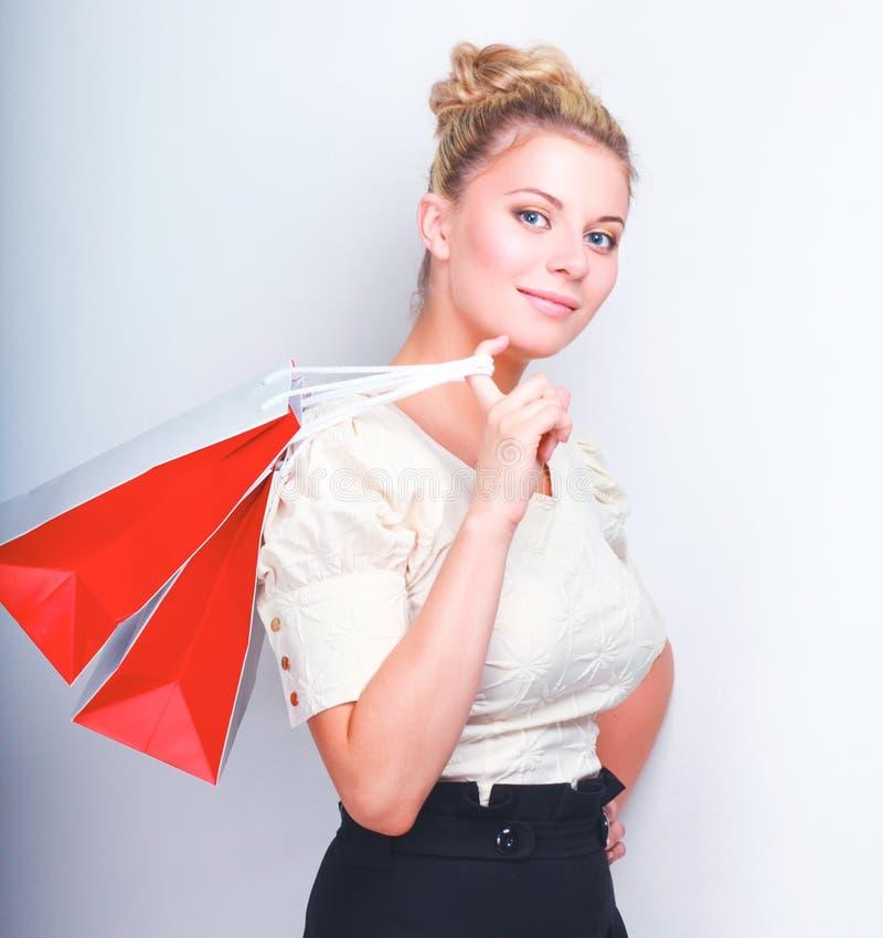 Женщина держа хозяйственные сумки против серой предпосылки стоковая фотография rf