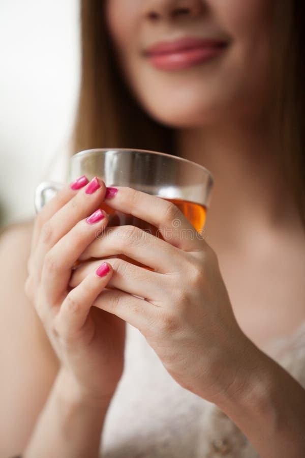 Женщина держа чашку чаю стоковое фото