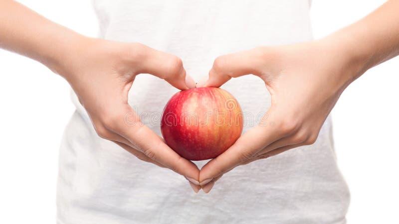 Женщина держа яблоко в руках сердца форменных стоковые изображения rf