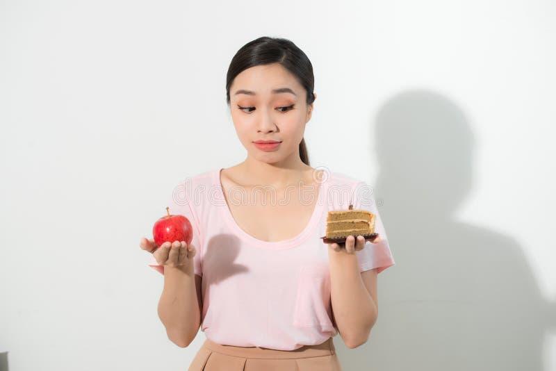 Женщина держит в выборе помадки торта руки и плода яблока стоковое изображение