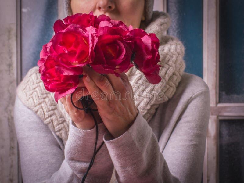 Женщина держит в ее цветках рук красных декоративных на foregroun стоковое изображение rf