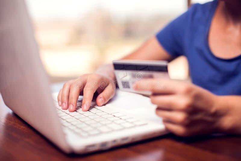 Женщина держит кредитную карточку и делает онлайн-платеж E стоковое изображение