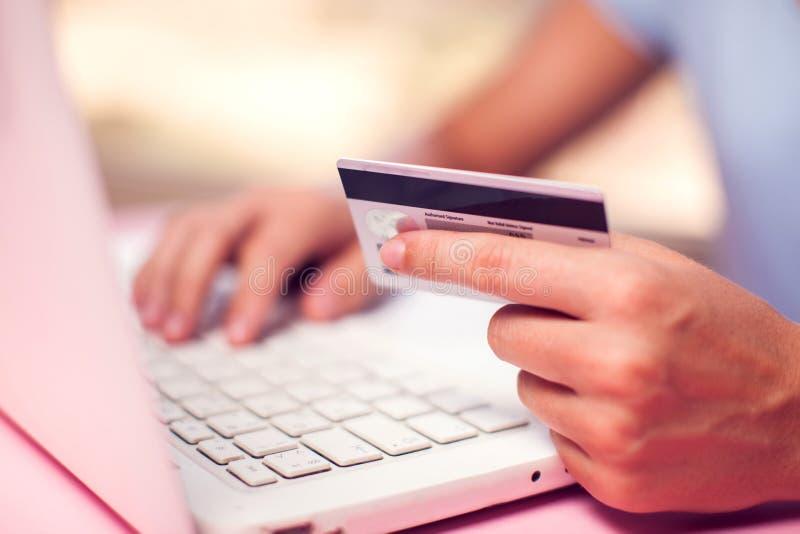 Женщина держит кредитную карточку и делает онлайн-платеж E стоковые изображения rf