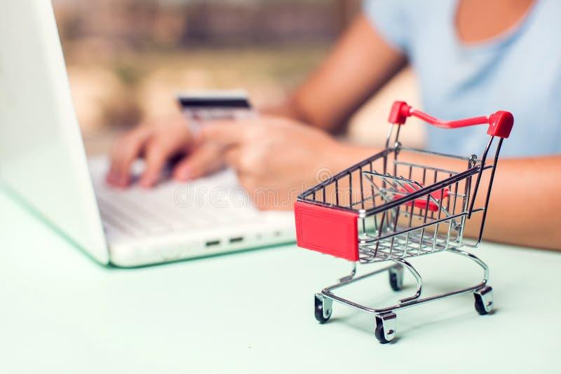 Женщина держит кредитную карточку и делает онлайн-платеж E стоковая фотография