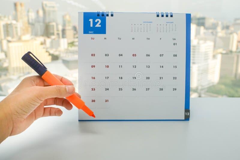 Женщина держит оранжевую ручку highlighter в руке для того чтобы отметить на дате назначения и встречи на календаре в декабре стоковая фотография rf