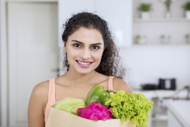 Женщина держит хозяйственную сумку с овощами стоковые изображения