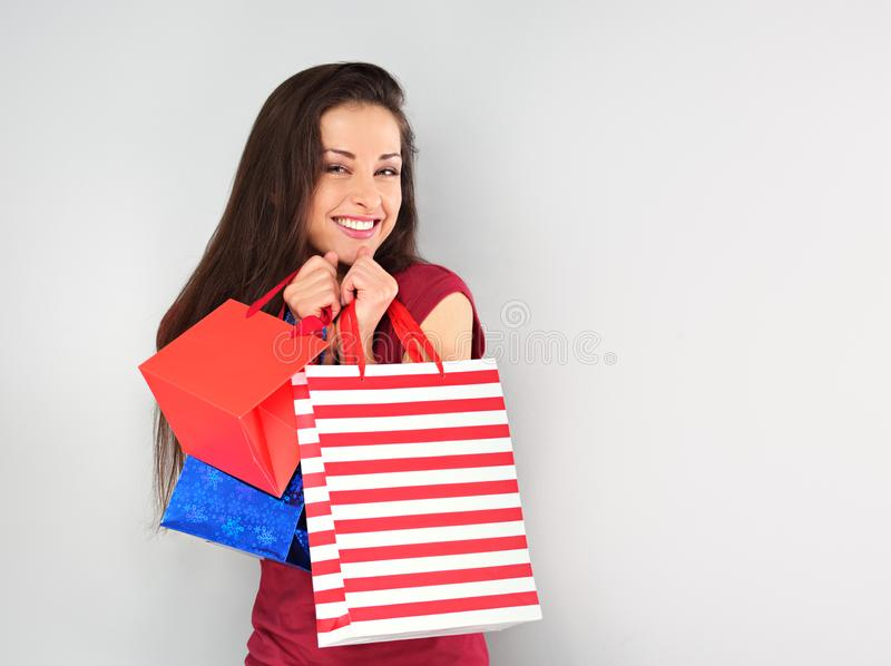 Женщина детенышей возбужденная зубастая усмехаясь с хозяйственными сумками на С Новым Годом! праздниках на голубой предпосылке стоковое изображение rf