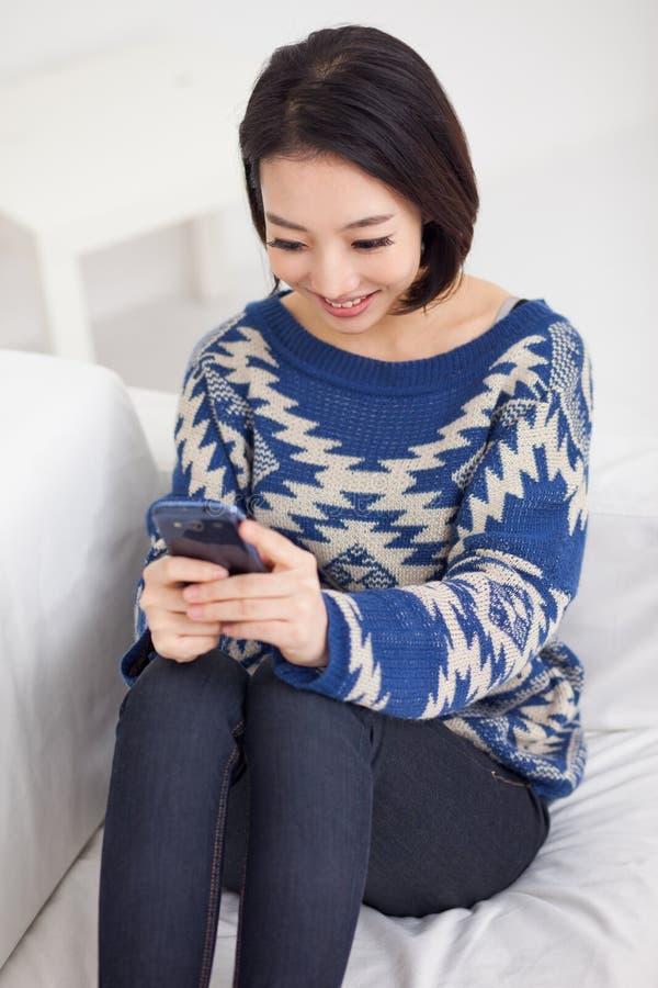 Женщина детенышей довольно азиатская с умным телефоном. стоковая фотография rf