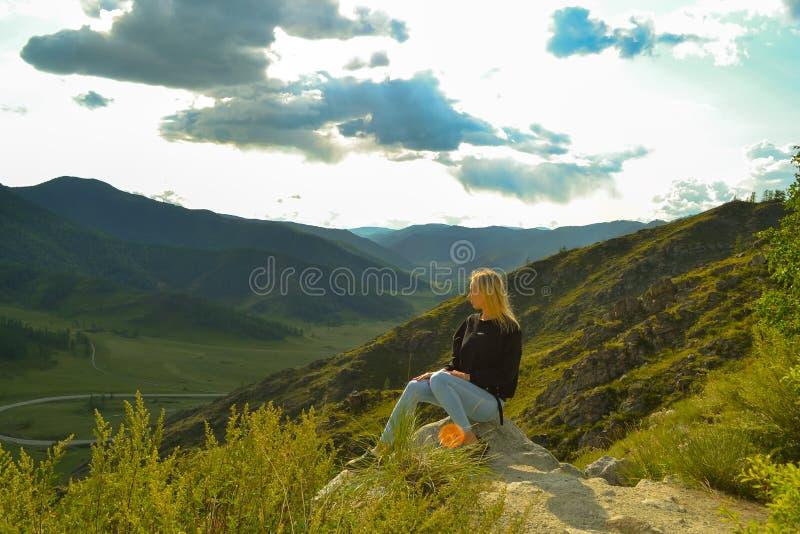 Женщина детенышей довольно белокурая сидит на утесе на солнечной теплой осени s стоковая фотография rf