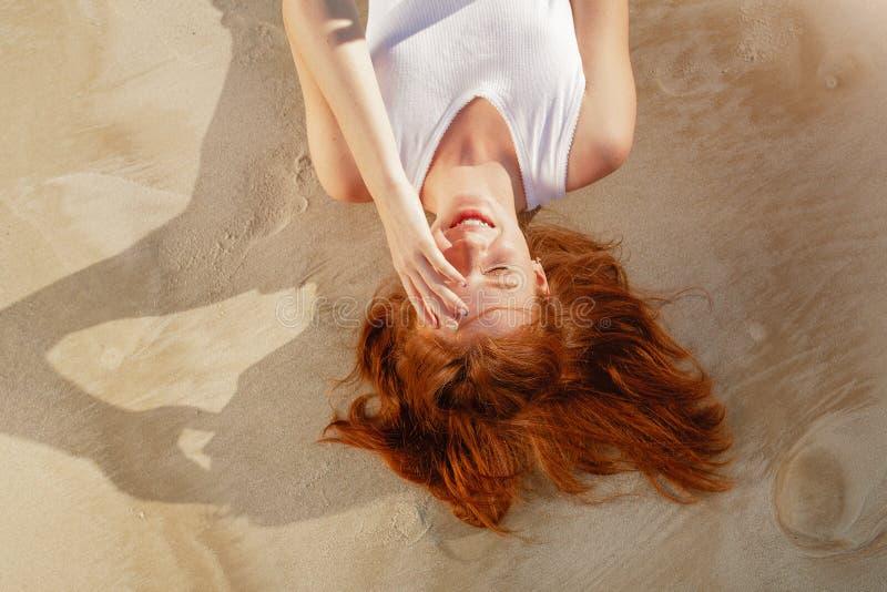 Женщина детенышей довольно рыжеволосая кладя на пляж стоковое фото