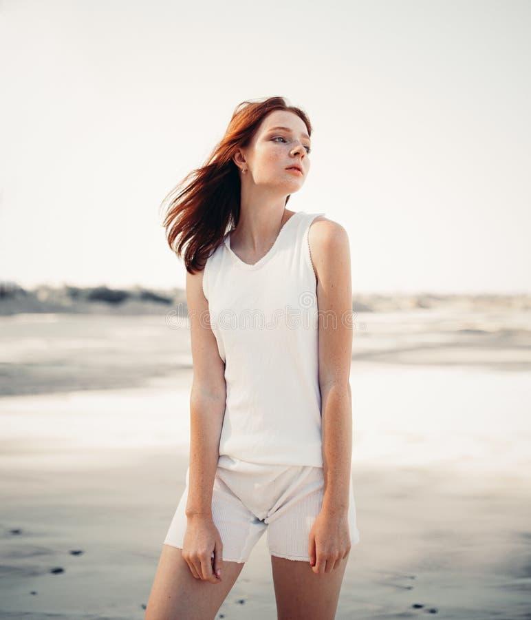 Женщина детенышей довольно рыжеволосая стоя на пляже стоковая фотография rf
