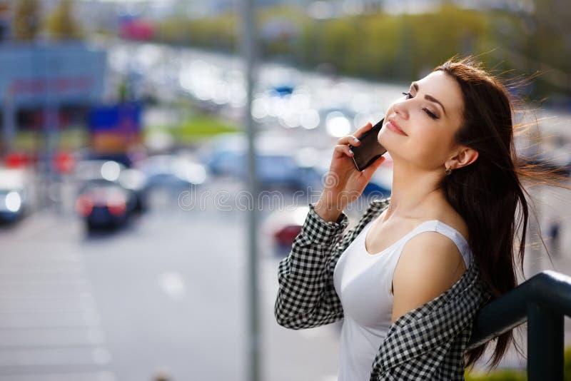 Женщина детенышей довольно стильная счастливая говоря на умном телефоне в c стоковые фотографии rf