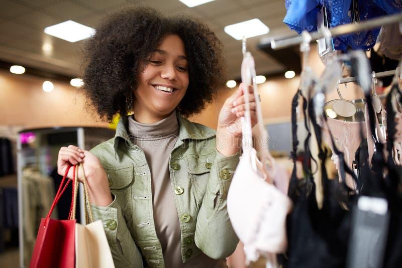 Женщина детенышей усмехаясь привлекательная Афро-американская выбирая правый размер бюстгальтера в магазине женское бельё Черная  стоковое фото