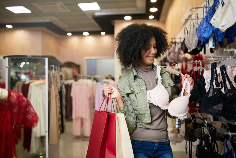 Женщина детенышей усмехаясь привлекательная Афро-американская выбирая правый размер бюстгальтера в магазине женское бельё Черная  стоковая фотография rf