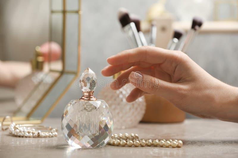 Женщина достигая для кристаллической бутылки роскошных духов стоковое фото