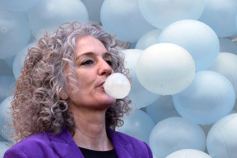 Женщина дует пузыри с жевательной резиной стоковые изображения rf