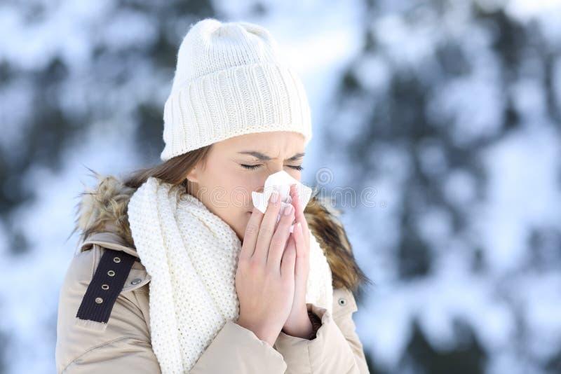 Женщина дуя в ткани в холодной снежной зиме стоковое фото rf