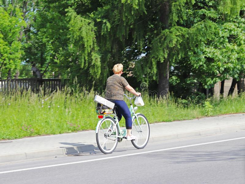 Женщина едет велосипед на стороне шоссе против предпосылки зеленых деревьев на солнечный, ясный день Альтернативное Masow ty стоковая фотография