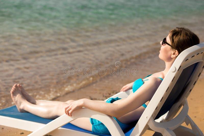 Женщина лежа на голубом deckchair стоковые фотографии rf