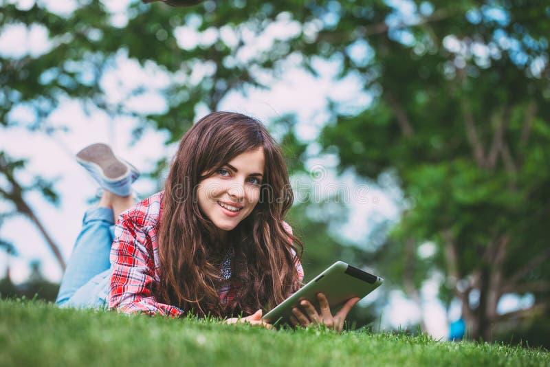 Женщина лежа на зеленой траве с таблеткой в парке стоковые изображения