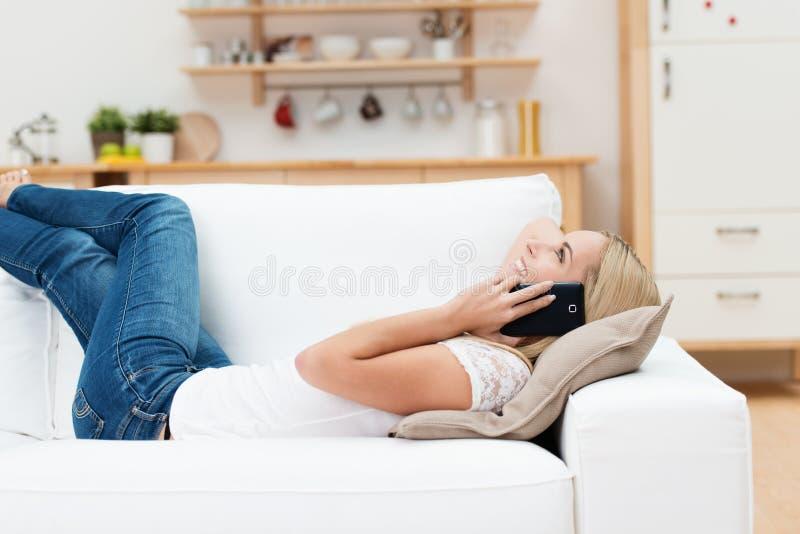 Женщина лежа на софе беседуя на телефоне стоковые изображения