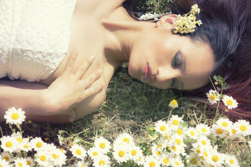 Женщина лежа на траве цветет закрытые глаза горизонтально стоковое изображение rf