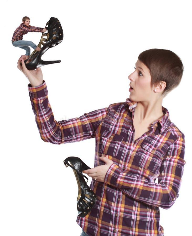 Женщина держа ботинок взобралась крошечной девушкой стоковая фотография rf