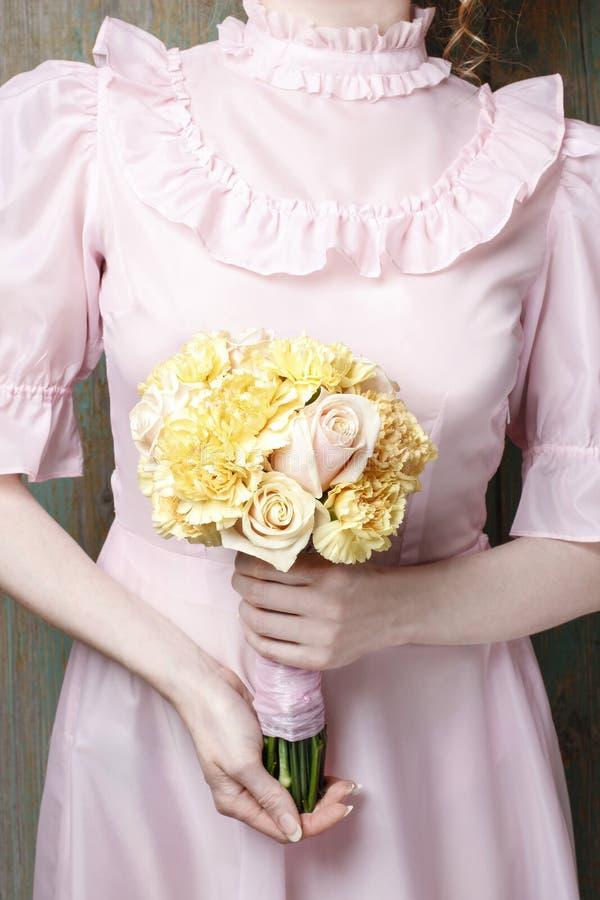 Женщина держа букет желтой гвоздики и розовых роз стоковое изображение