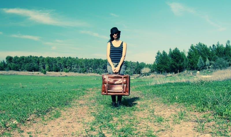 Женщина держа винтажную сумку стоковые фото