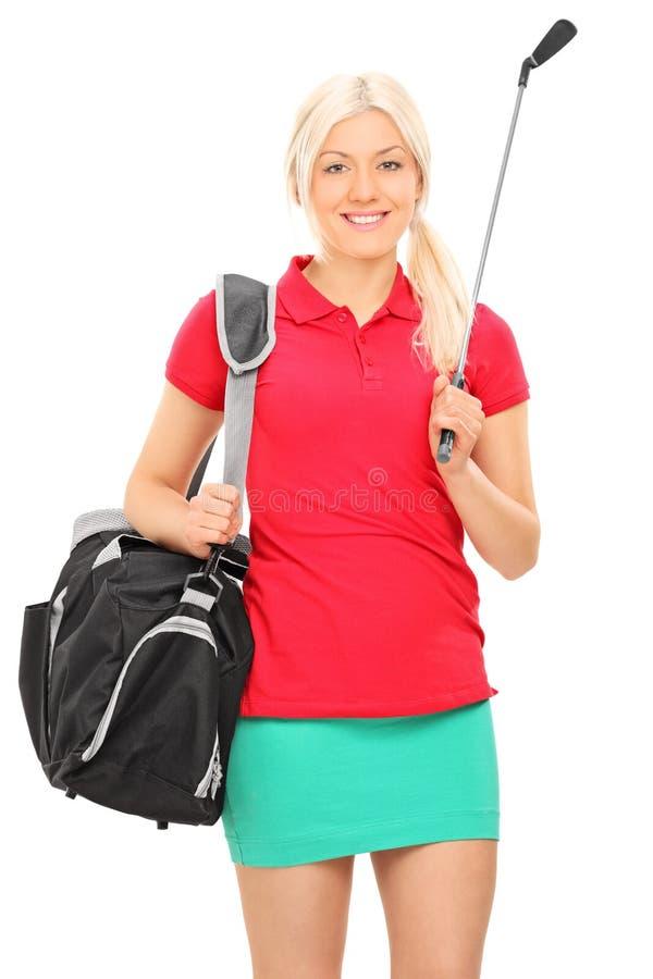 Женщина держа гольф-клуб и нося сумку стоковые изображения