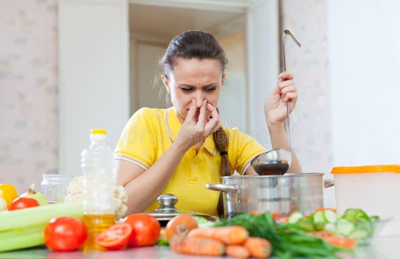 Женщина держа ее нос из-за плохого запаха от супа стоковое фото rf