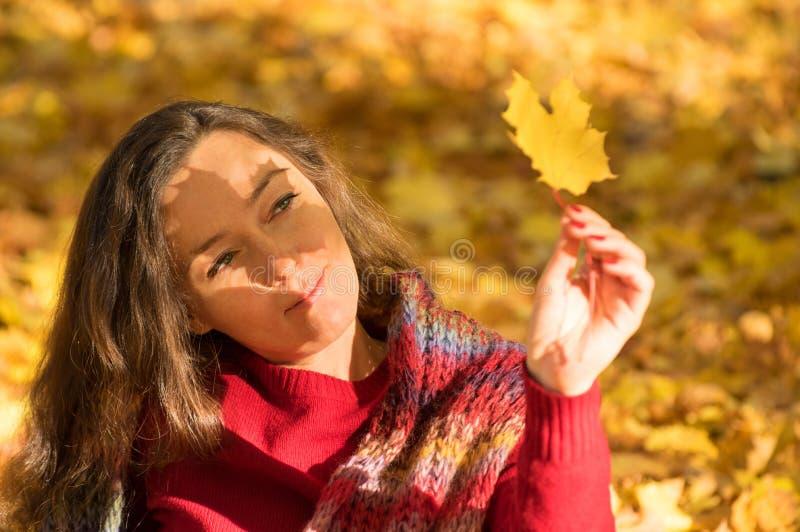 Женщина держа желтый кленовый лист на лесе осени стоковые фотографии rf