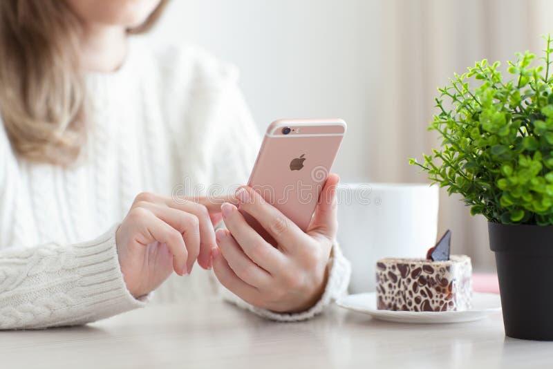 Женщина держа золото iPhone 6 s розовое в кафе стоковые фото