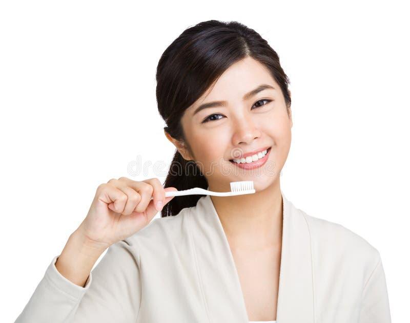 Женщина держа зубную щетку и улыбку стоковые изображения rf