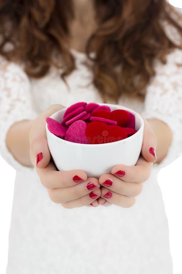Женщина держа кофейную чашку заполнила с сердцами стоковое изображение