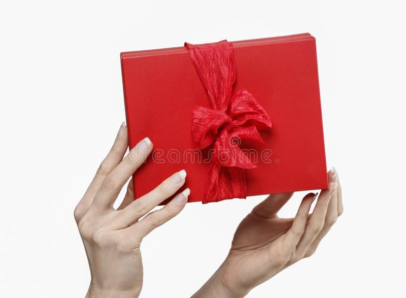 Женщина держа красную присутствующую коробку с большим смычком стоковое изображение