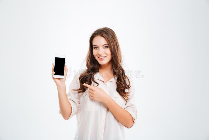 Женщина держа мобильный телефон пустого экрана и указывая палец стоковое изображение