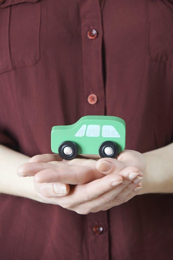 Женщина держа модельный автомобиль в ладони руки стоковые изображения rf