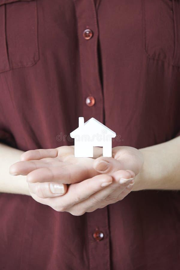 Женщина держа модельный дом в ладони руки стоковое изображение