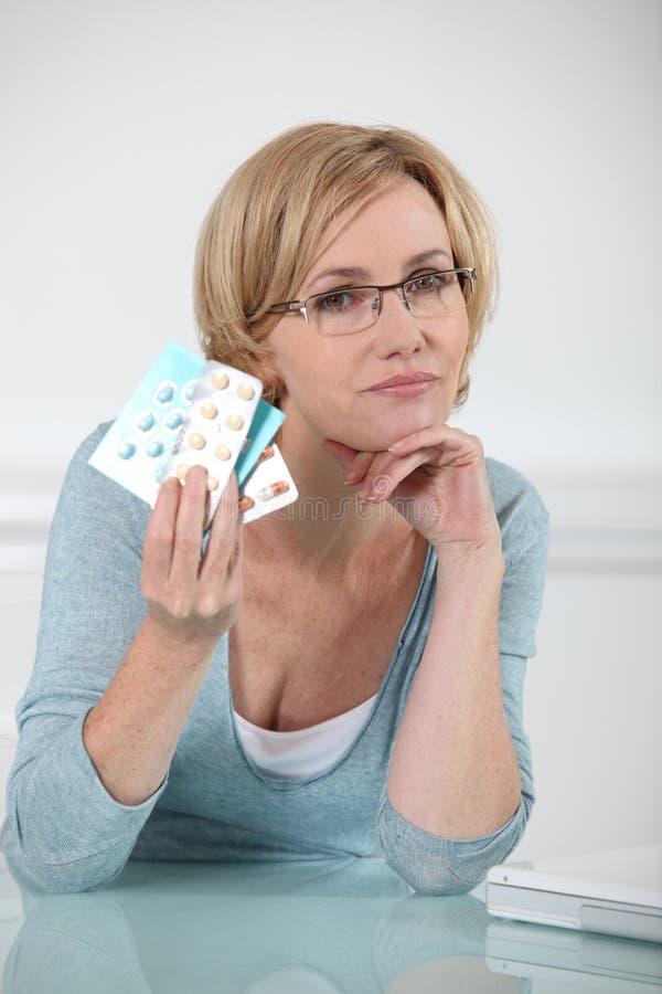 Женщина держа отпускаемые по рецепту лекарства стоковая фотография rf