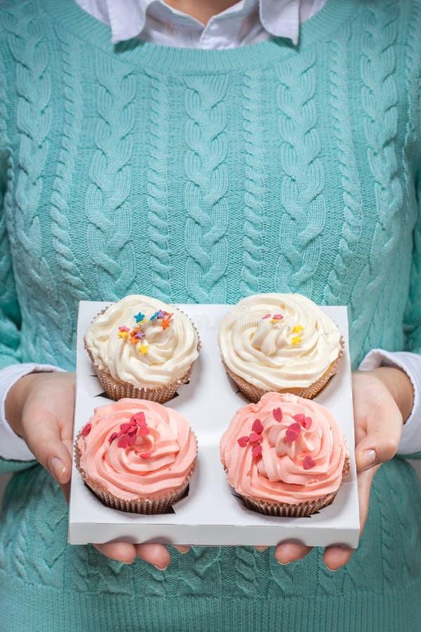 Женщина держа пирожные в руках изолированных на белизне стоковая фотография rf