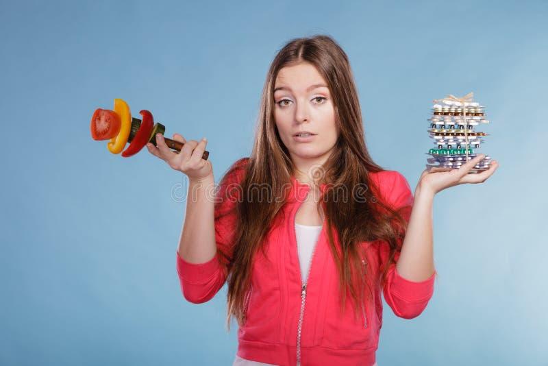 Женщина держа пилюльки и овощи здоровье внимательности рукояток изолировало запаздывания стоковые фото